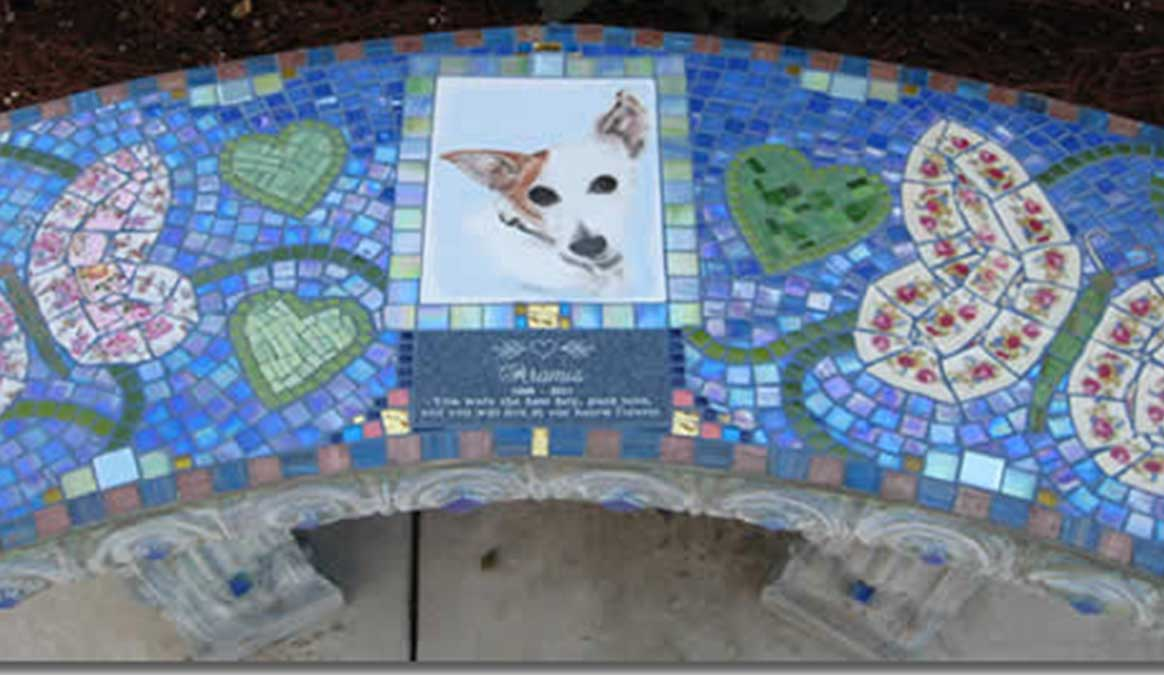 Mosaic Memorial Garden Bench with Portrait Tiles of Aramis' Buterflies and Hearts with handpainted portrait tile Closeup by Water's End Studio Artist Linda Solby